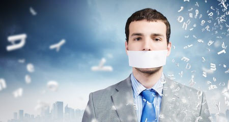 Young handsome businessman with adhesive tape on mouth photo