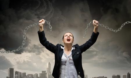 Imagen de la empresaria en la ira rompiendo la cadena de metal Foto de archivo - 24935294