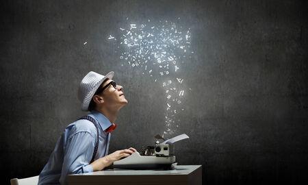 Jonge grappige mens in glazen schrijven op typemachine