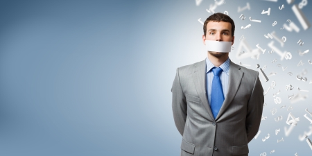 incapacity: Young handsome businessman with adhesive tape on mouth Stock Photo