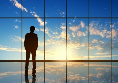 corporate responsibility: Silhouette of businessman against panoramic office window Stock Photo