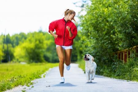 perro corriendo: Joven atractiva chica de deporte corriendo con el perro en el parque