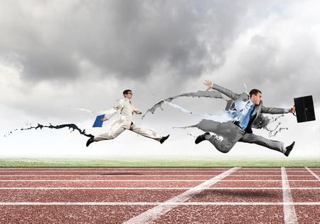 business rival: Funny image of young businesspeople running at stadium Stock Photo