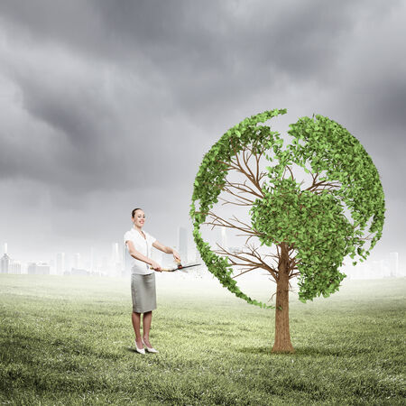 Young businesswoman cutting tree with scissors in shape of Earth planet Stock Photo - 24966569