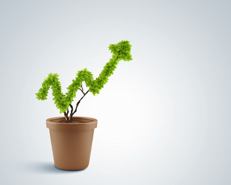 growing success: Image of human hands holding plant shaped like arrow Stock Photo
