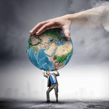 el mundo en tus manos: Imagen de joven empresario bajo la presi�n de la tierra del planeta elementos de esta imagen proporcionada por la NASA est�n Foto de archivo