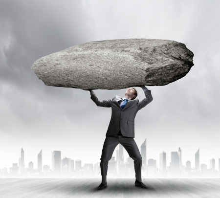 exertion: Powerful businessman holding huge stone above head Stock Photo