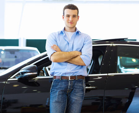 Handsome young man consultant at car salon standing near car photo