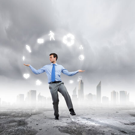 symbol of life: Young businessman juggling with conceptual symbols against city background Stock Photo