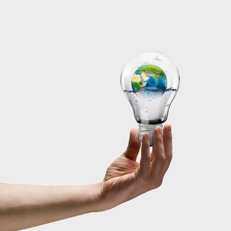 Image of human hand holding bulb with earth planet inside photo