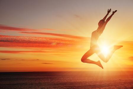 bailarines silueta: Silueta del bailarín que salta contra la ciudad de las luces de la salida del sol Foto de archivo