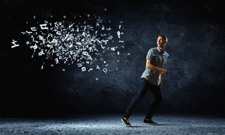 Funny image of young man trying to escape from flying letters photo