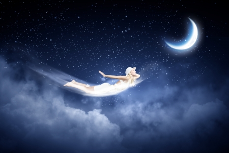 Young blond girl flying in night sky