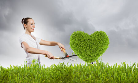 Young happy businesswoman cutting bush with grass cutter photo