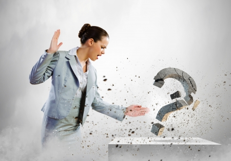 Image of businesswoman destroying with arm stone question mark Stock Photo
