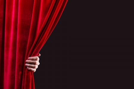 赤いカーテンの場所テキスト用開き手のクローズ アップ