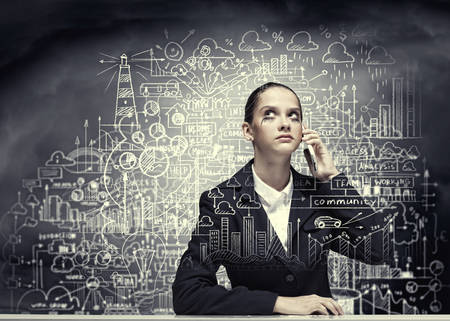 Young upset businesswoman talking on mobile phone photo