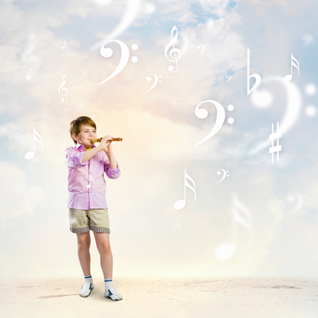Image of little cute boy playing on flute against cloudy background photo