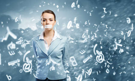 incapacity: Young speechless businesswoman with adhesive tape on mouth Stock Photo