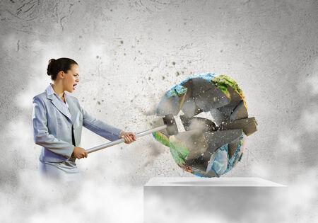 Image of businesswoman crashing globe with hammer  Ecology concept Stock Photo
