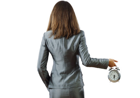Back view of businesswoman holding alarm clock against white background photo