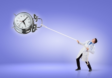 Image of handsome doctor pulling clock with rope photo