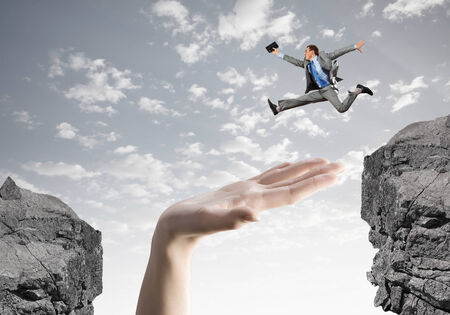 Young successful businessman jumping over gap  Risk and challenge concept photo