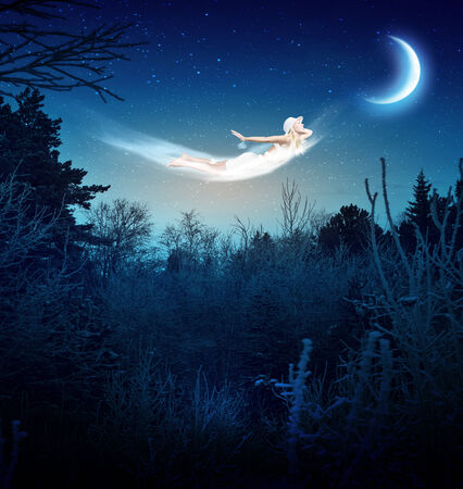Young blond girl flying in night sky photo