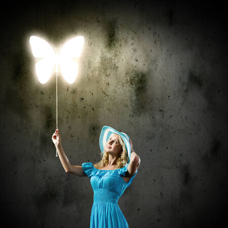 Young pretty woman in blue hat and dress holding balloon photo
