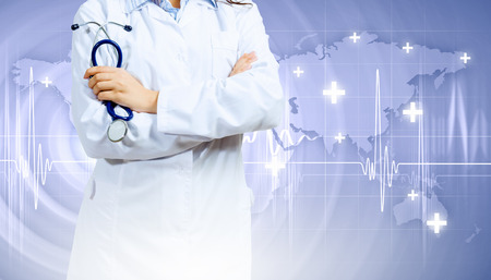 Image of doctor holding stethoscope against media background photo