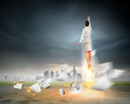 Image of businesswoman flying up into sky