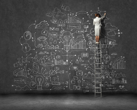 Rear view of businesswoman standing on ladder and drawing business sketch on wall photo