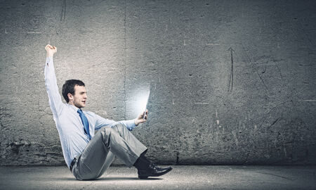 Young joyful handsome businessman using tablet pc Stock Photo - 25000183