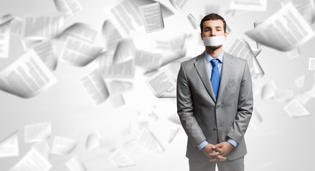 Young handsome businessman with adhesive tape on mouth Stock Photo