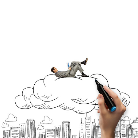 Young relaxed businessman lying on cloud and reading book photo