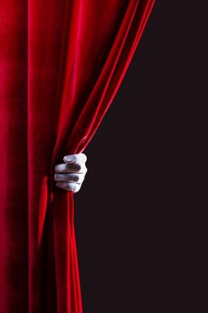 Close-up van de hand in witte handschoen opent het gordijn Voor tekst