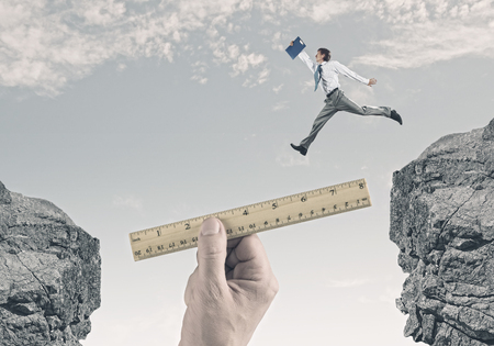 Young successful businessman jumping over gap  Risk and challenge concept