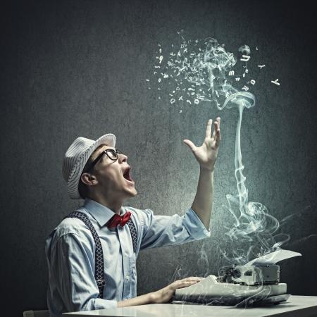 Junge lustige Mann mit Brille schreibt auf Schreibmaschine Standard-Bild