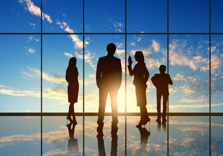 woman window: Silhouettes of businesspeople standing against panoramic office window