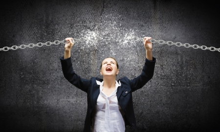 Image of businesswoman in anger breaking metal chain Reklamní fotografie - 25000475