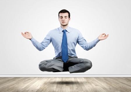 Jonge zakenman zitten in lotus houding en mediteren