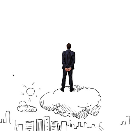 Rear view of businessman standing on cloud and looking at city