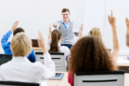 Young teacher in classroom standing in front of class photo
