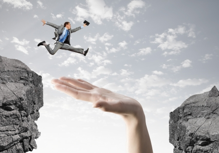 impediment: Young successful businessman jumping over gap  Risk and challenge concept