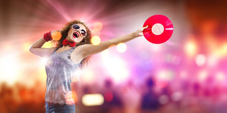 Young pretty girl dj at disco party holding vinyl photo