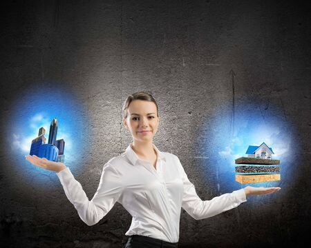 alternative living: Image of businesswoman holding items on palm  Urban or country