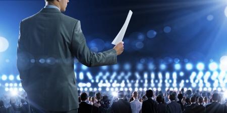 Vue arri�re d'homme d'affaires haut-parleur debout sur le podium dans les lumi�res