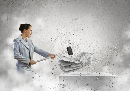 frenzy: Image of businesswoman crushing with hammer pile of keyboards