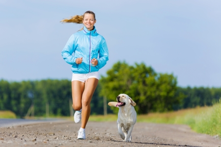 Young healthy girl running outdoor with her dog photo