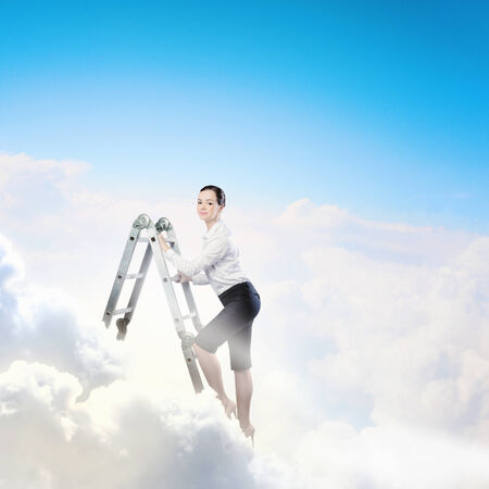 goal oriented: Image of young ambitious businesswoman climbing ladder  Promotion concept